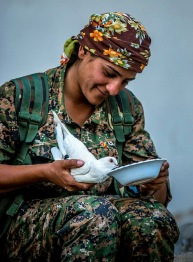 Kurdish woman fighter feeds a dove that is resting in the palm of her right hand.