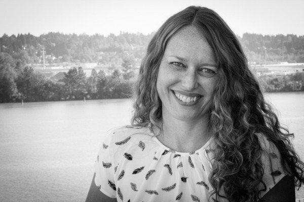 This photo shows a headshot of Lisa Manfield smiling with a lake backdrop.