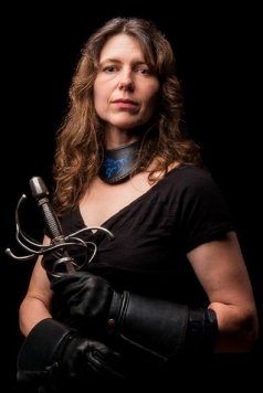 This photo depicts Jennifer Landels in her swordplay outfit with both hands holding onto the sword, making it point downwards.