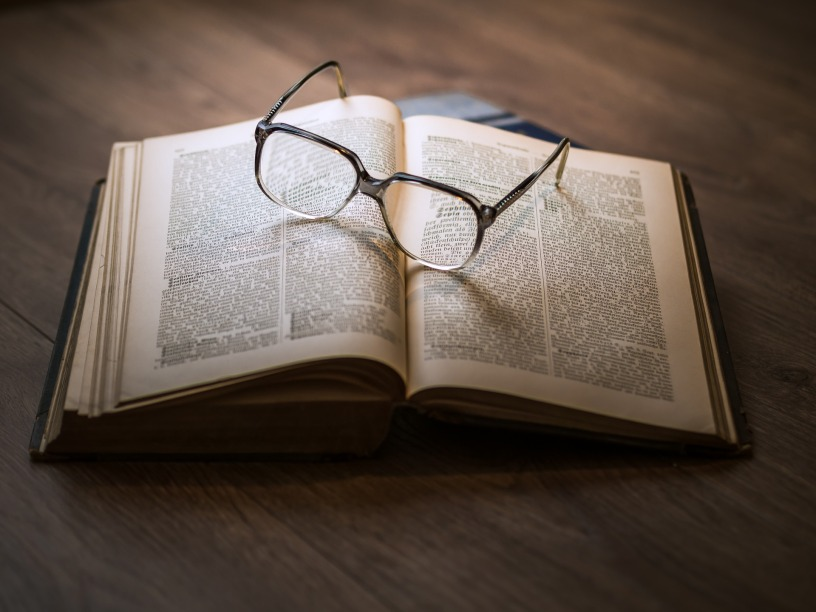 This image depicts an opened German book laying flat on a wooden floor with a pair glasses sitting diagonally on top of it.