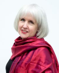 Framed by her short white hair, Moira White is smiling in this photo while wearing a long, red scarf and black shirt.