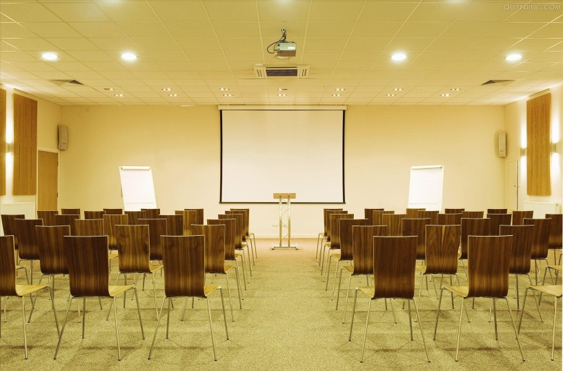 The photo depicts a large conference room full of rows of chairs in front of a flip chart, a projector, and a projection screen.