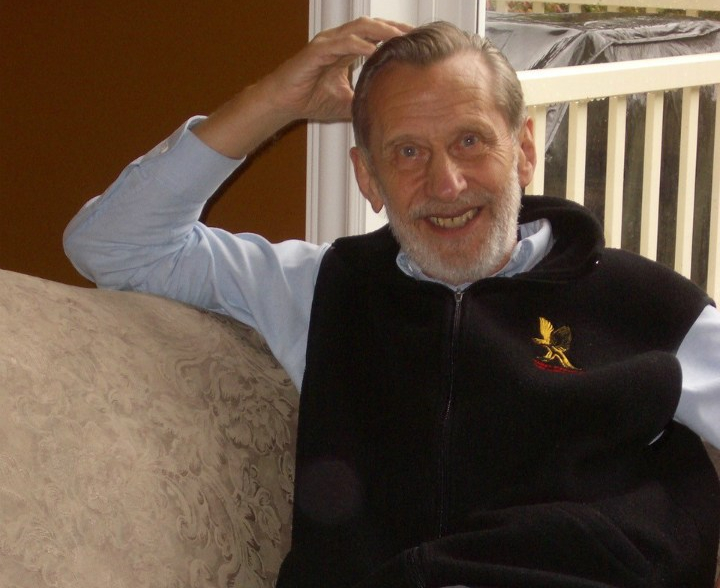 A photo presents the late David Harrison relaxing on a couch in a dark vest, light, long-sleeved blue shirt, and dark pants.