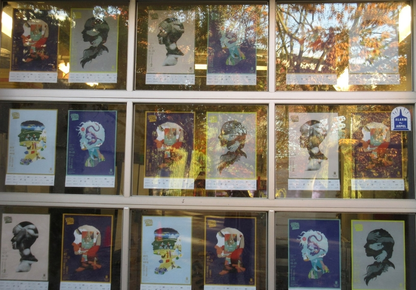 Three rows of six posters with differently shaped heads face toward a window that is reflecting tree branches and fall leaves.