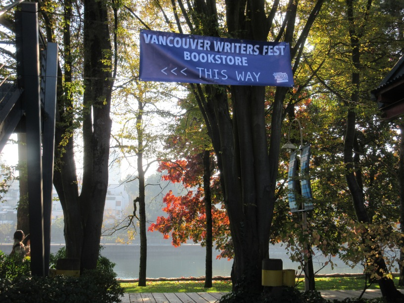 "A blue banner with the words ""Vancouver Writers Fest Bookstore"" is surrounded by brilliant light and trees near a quay-like environment."