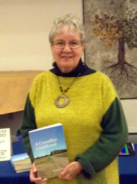 "This photo depicts a headshot of Carolyn Redl in a yellow and dark green top wearing a necklace and smiling warmly while holding a copy of her memoir, ""A Canadian Childhood."""