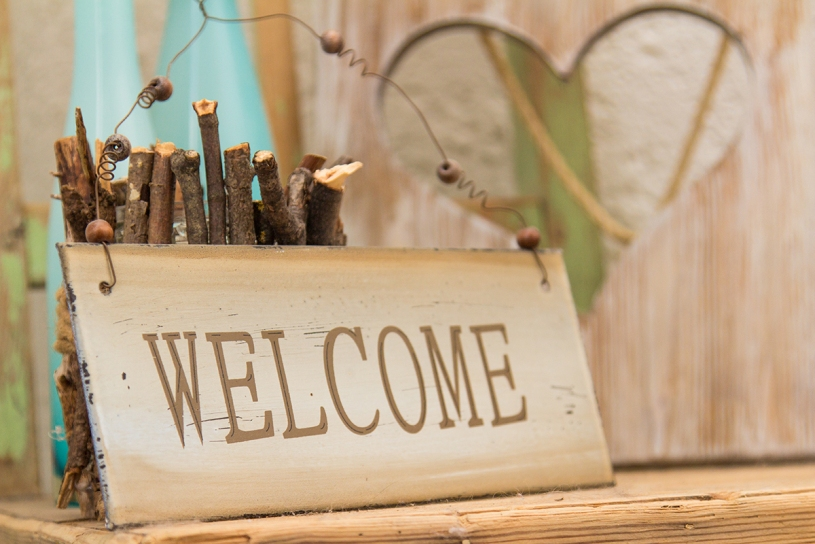 A rustic wooden WELCOME sign is standing on a wooden shelf in front of a wood panel with a cut out heart offering a warm country welcome.