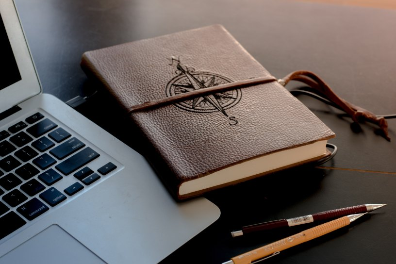 A leather notebook with a navigation symbol rests against the edge of a laptop on a brown, shiny surface near two mechanical pencils.