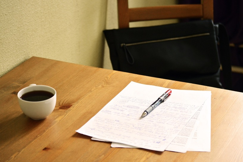 A wooden chair with a cushion on it sits next to a wooden table that has a cup of coffee, marked up papers, and a red pen on its surface.