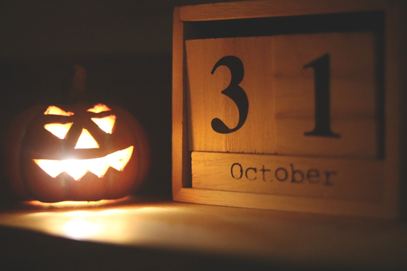 A lit jack-o'-lantern sits next to a wooden frame that encircles two wooden rectangular shapes that display the date October 31.