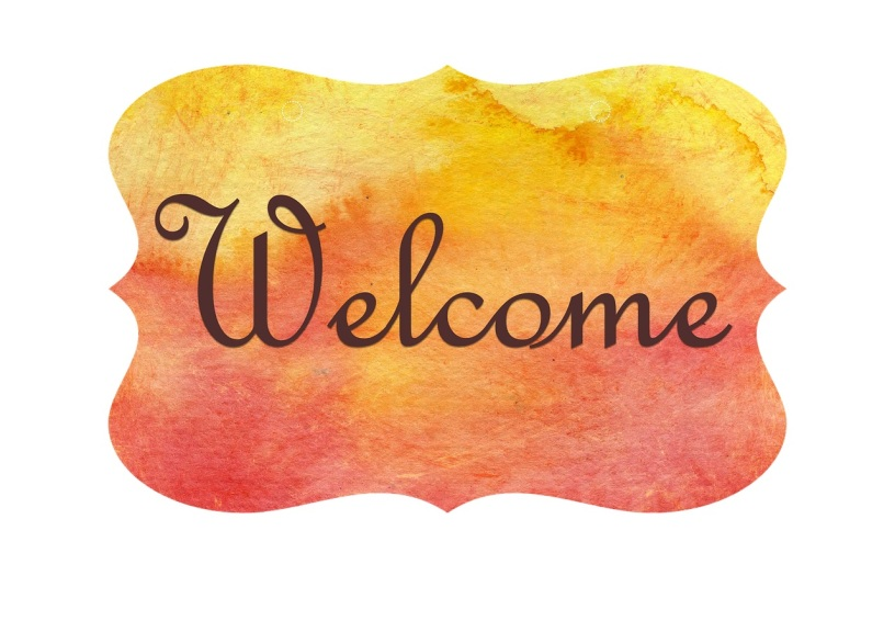 "An orange-yellow sign displays the curly words ""Welcome"" in a dark brown font colour."