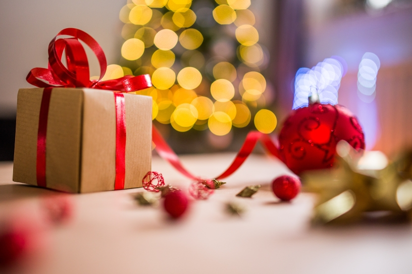 A gift covered in brown wrapping paper and red ribbon sits in the forefront while a blurred Christmas tree rests in the background.
